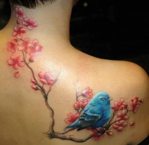 קעקוע ציפור כחולה לצד פריחה